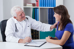 Helpful physician. Helpful elderly physician and his happy female patient Stock Images