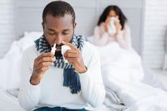 Ill man using helpful nasal drops Royalty Free Stock Images