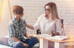 Helpful psychologist talking with a school boy