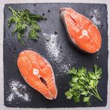 Helpful sports foods, cooking two fresh salmon steak with herbs and spices,on  cutting board stone, top view close up Stock Photography