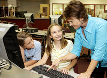 Helpful Teacher. A helpful teacher showing school kids how to use the computer stock image