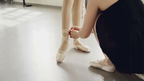 Helpful teacher is putting pointe-shoes on little student`s feet tying ribbons around small legs before ballet lesson. Helpful female teacher is putting pointe stock video