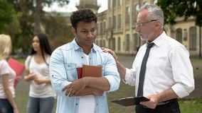 Helpful teacher supporting upset student who failed test, support and assistance stock photography