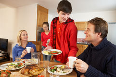 Helpful Teenage Children Serving Food. To Parents In Kitchen Royalty Free Stock Image