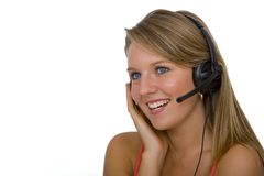 Helpful Telephonist Too. A beautiful young blonde telephonist smiling and speaking on a headset Royalty Free Stock Images