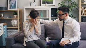 Helpful therapist comforting stressed woman crying in office giving paper tissue. Helpful male therapist is comforting stressed woman crying in office giving her stock footage