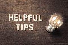 Helpful Tips Idea. Helpful Tips text with glowing light bulb on wood texture royalty free stock photos