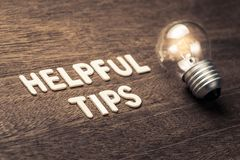 Helpful Tips Idea. Helpful Tips text with glowing light bulb on wood texture Royalty Free Stock Image