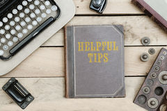 Helpful Tips on old book cover at office desk with vintage items Royalty Free Stock Image