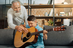 Happy grandfather giving grandson tips on playing guitar Stock Photos