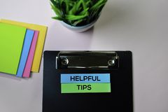 Helpful Tips text on sticky notes with office desk concept stock image