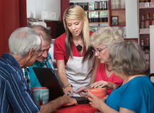 Helpful Waitress with Seniors on Laptop Royalty Free Stock Photography