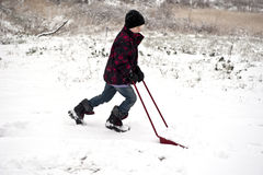 Helpful young boy shoveling snow. Young boy plowing away snow with a little shovel Royalty Free Stock Photography