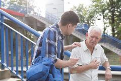 Helpful young man. Helpful young men talking with male retiree Royalty Free Stock Image