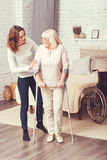 Helpful young woman helping disabled old mother at home. Supporting rehabilitation process. Accurate positive young daughter standing in the bedroom and taking Royalty Free Stock Photography