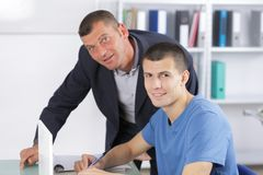 Helpfuly teacher and happy student smiling at camera Royalty Free Stock Image