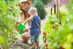 Helphing mamma för gulligt litet barn i trädgården royaltyfri bild