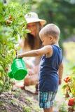 Helphing mamma för gulligt litet barn i trädgården arkivfoto