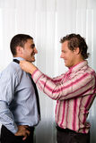 Helping. Homosexual couple, man helping with the tie Royalty Free Stock Images