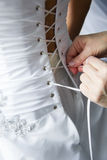 Helping the bride with bride's white corset Stock Photos