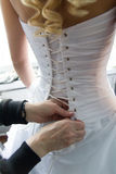 Helping the bride with bride's white corset Stock Images