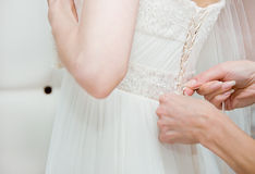 Helping the bride to put her dress on Royalty Free Stock Images