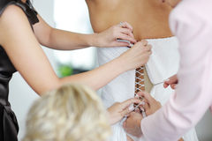 Helping a bride to put her wedding dress on Royalty Free Stock Image