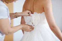 Helping the bride to put her wedding dress Royalty Free Stock Image