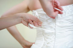 Helping the bride to put her wedding dress Royalty Free Stock Photography