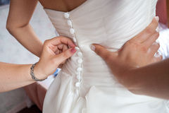 Preparation bride. Helping the bride to put her wedding dress Royalty Free Stock Images