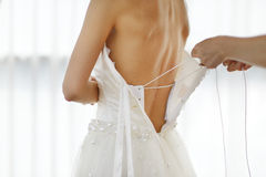 Helping the bride to put her wedding dress Stock Photos