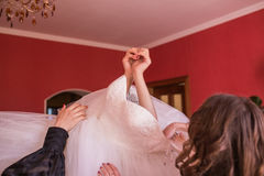 Helping bride to put her wedding dress on Stock Photography