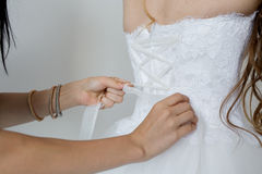 Helping the bride to put her wedding dress Stock Photography