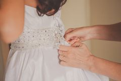 Helping the bride to put her wedding dress on Royalty Free Stock Images