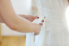 Helping the bride to put a  wedding dress on Stock Photo