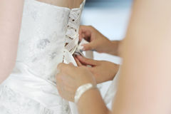 Helping the bride to put a wedding dress on Stock Photos