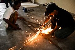 Helping Carpenter. An immigrant from Myanmar, helping to hold the metal being cut by a carpenter who was hired by the IOM to make the cooking table Royalty Free Stock Image