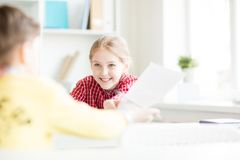 Helping classmate. Cute smiling schoolgirl looking at her classmate and passing him paper with text which may help royalty free stock image