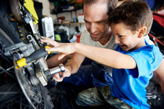 Helping dad with tools. A boy helping his dad with fixing a motorcycle in the garage Stock Photography