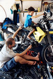 Helping dad with tools. A boy helping his dad with fixing a motorcycle in the garage Royalty Free Stock Image
