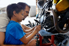 Helping dad with tools. A boy helping his dad with fixing a motorcycle in the garage Stock Photo