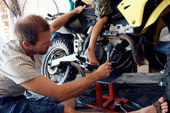Helping dad with tools. A boy helping his dad with fixing a motorcycle in the garage Royalty Free Stock Photo