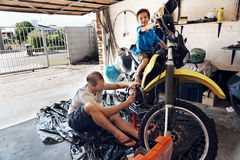 Helping dad with tools. A boy helping his dad with fixing a motorcycle in the garage Royalty Free Stock Photography