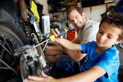 Helping dad with tools. A boy helping his dad with fixing a motorcycle in the garage Royalty Free Stock Photos
