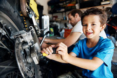 Helping dad with tools. Portrait of a boy helping his dad with fixing a motorcycle in the garage Stock Image