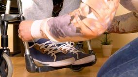 Helping a disabled man in wheelchair closeup. Assistance for a disabled man in wheelchair, tying shoes. Closeup 4k