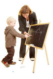 Helping with drawing. Boy drawing on a blackboard and teacher helping Stock Photo