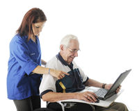 Helping the Elderly with His Computer Royalty Free Stock Photography