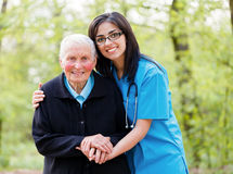 Helping Elderly Peoplee. Portrait of caring nurse helping elderly lady holding her hands stock photos