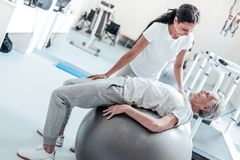 Joyful trainer helping her patient exercise. Helping while exercising. Exuberant old wrinkled grey-haired men lying on a ball for exercises and a smiling young Royalty Free Stock Photo